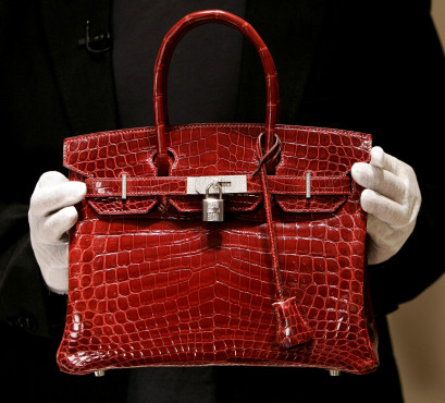 New York, UNITED STATES: A employee holds a 129,000 USD crocodile Hermes Birkin Bag for the press to see during a private opening for the new Hermes store on Wall Street in New York 21 June 2007. The store which is located at 15 Broad Steet is across the street from the New York Stock Exchange. The store is one of several luxury shops opening near Ground Zero as part of a revitalization project in the area. AFP PHOTO/ TIMOTHY A. CLARY (Photo credit should read TIMOTHY A. CLARY/AFP/Getty Images)